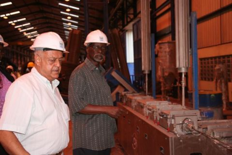 Former Internal Affairs Minister Kirunda Kivejinja (R) is taken around Roofing Limited Namanve plant by by MD Lalani some years ago