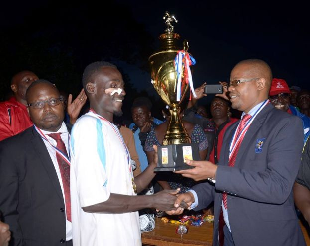 Moses Magogo, FUFA president hands the CNOOC Bunyoro Amasaza Cup 2016 trophy to the Buruuli team captain Baraka Musana at Sir Tito Winyi grounds, Hoima