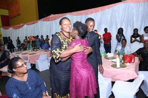 Daphne Kato the principal of Kampala School hugs a former pupil