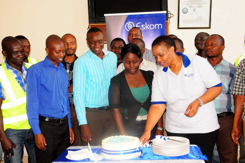 Eskom M.D (In white T-Shirt) and finance director (in blue shirt) join the trainees in cutting the a farewell cake