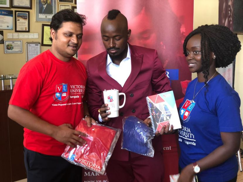 Ykee Benda receiving gifts from Victoria University VC and Guild Presidet Peggy Maria Nabunya