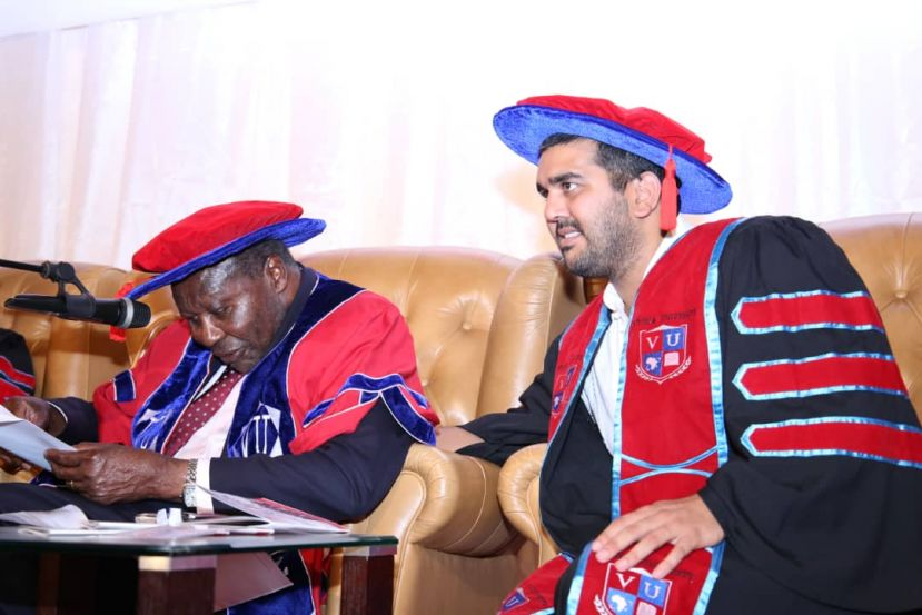 Victoria University promoter Rajiv Ruparelia (L) gestures while Chancellor Dr. Martin Aliker reads his speech script