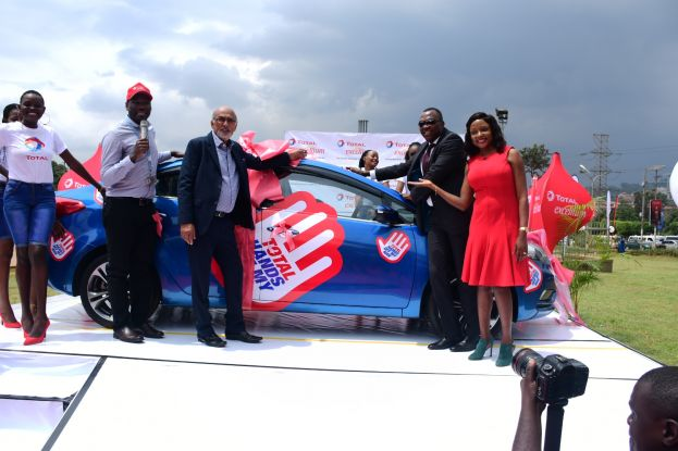 Total Uganda retail and marketing team led by the Managing Director Obi iMEMBA (2nd R) show off the grand prize KIA car at the launch of a two months long nationwide Total Excellium Epic Battle campaign