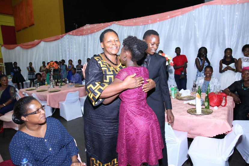 Ms Daphine Kato hugs a former pupil who excelled in last years PLE at a farewell party