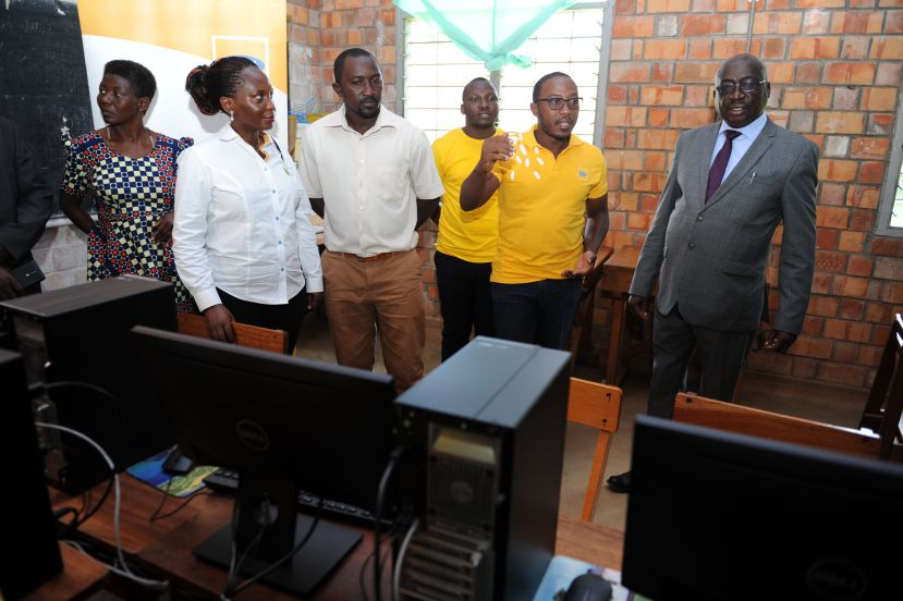 MP Bategeka (R) touring the ICT laboratory with  MTN officials at St Simon Peters