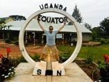 A tourist takes a photo at the Uganda equator
