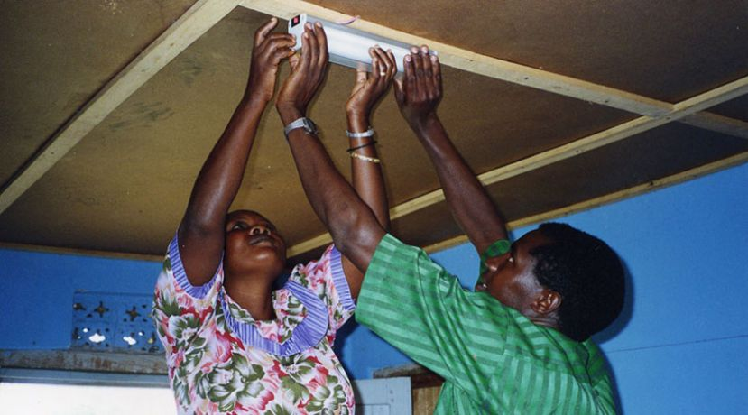 A couple fixing an electricity tube in a house in Uganda