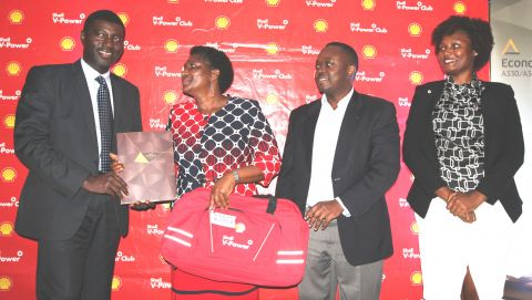 Toyin Alaran, General Manager Uganda, Etihad Airways hands over travel documents to Margaret Mugerwa, a winner of the Shell V-Power Formula 1 promotion