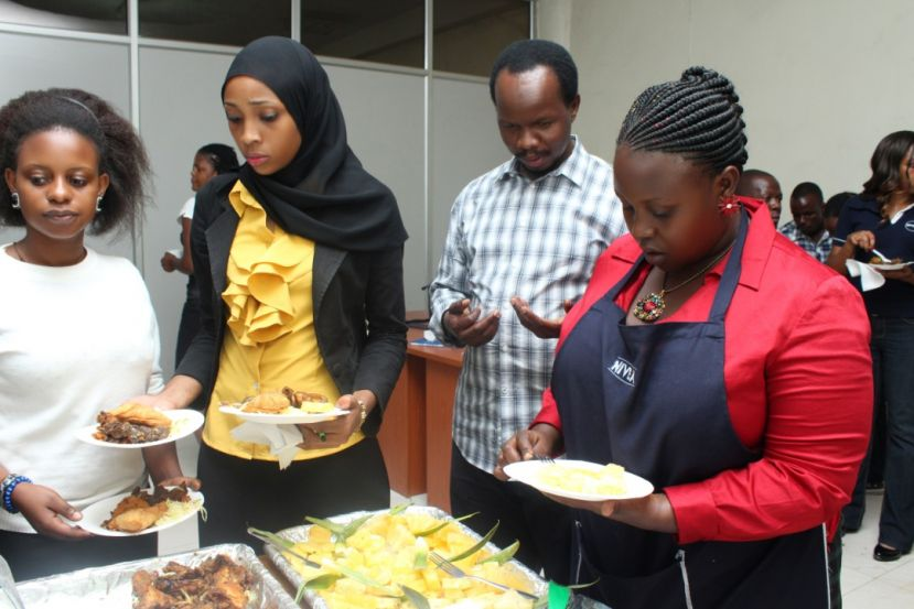 Businessman Chris Mutinye sharing a meal with some of his employees when the company was still running smoothly