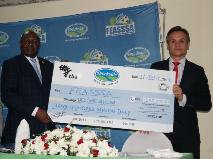 Oliver Mary, Marketing Director Brookside Limited hands over a dummy cheque of 1.2 Billion Ushs to the Minister of State for Sports, Hon. Bakkabulindi Charles