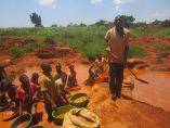 Children wash stone to collect gold nuggets