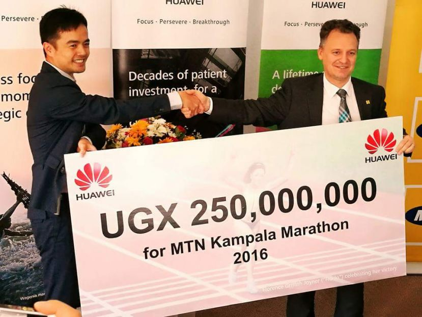 Huawei MD Mr. Stanley Chyn (L) giving a dummy cheque of UGX250,000,000 to Mr. Wim Vanhellepute (R) the MTN Chief Executive Officer.