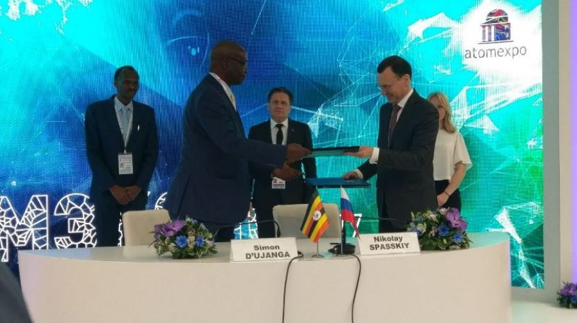 Uganda's minister Simon D'Ujanga exchanges documents with Russian officials